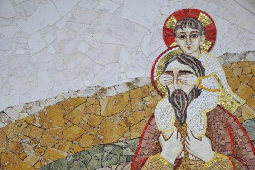 Sveti Krištof na steni kapelice pred farno cerkvijo v Št. Petru na Vašinjah. Pred kratkim nastala umetnina duhvnika in umetnika Marka Rupnika je enkratna zaradi tega, ker Jezus zapira oči sv. Krištofu.  (Gotthardt)