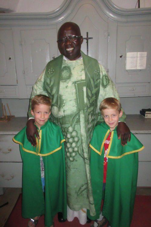 Pfarrer Eliseo Ovure mit Ministranten (© Foto: RK)