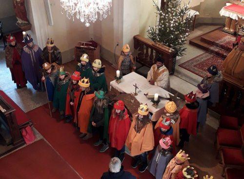 Die Sternsinger stehen um den Altar